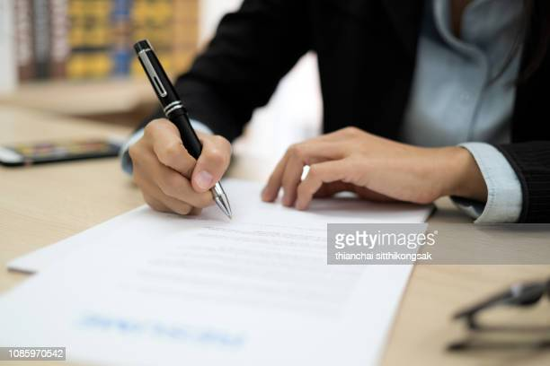 woman signing job contract - parte do corpo humano imagens e fotografias de stock