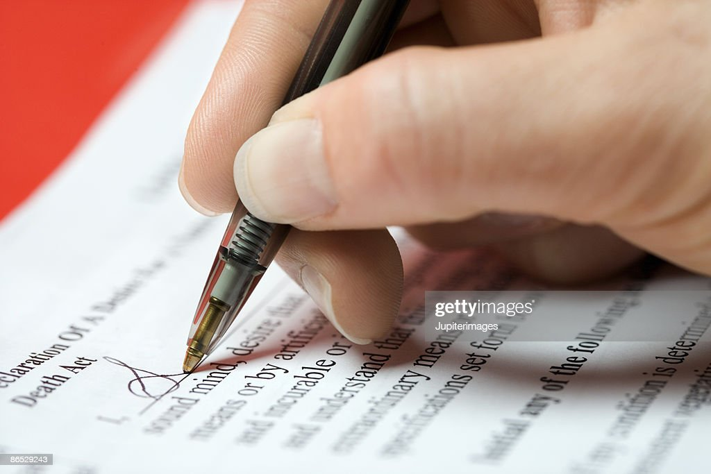 Woman signing legal document : Stock Photo