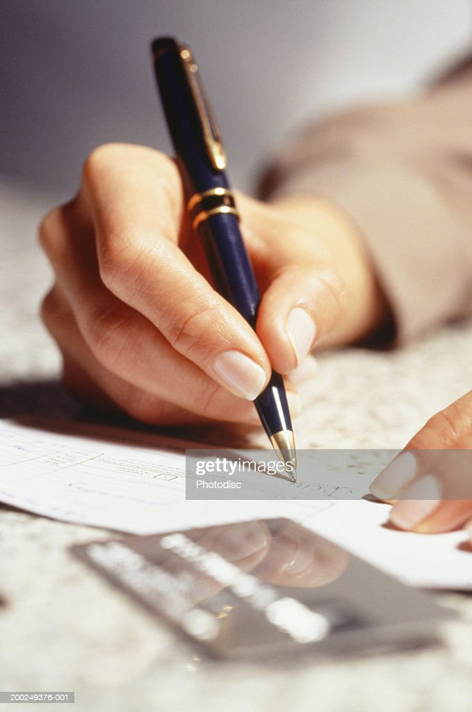Woman signing receipt, Close-up of hand : Stock Photo