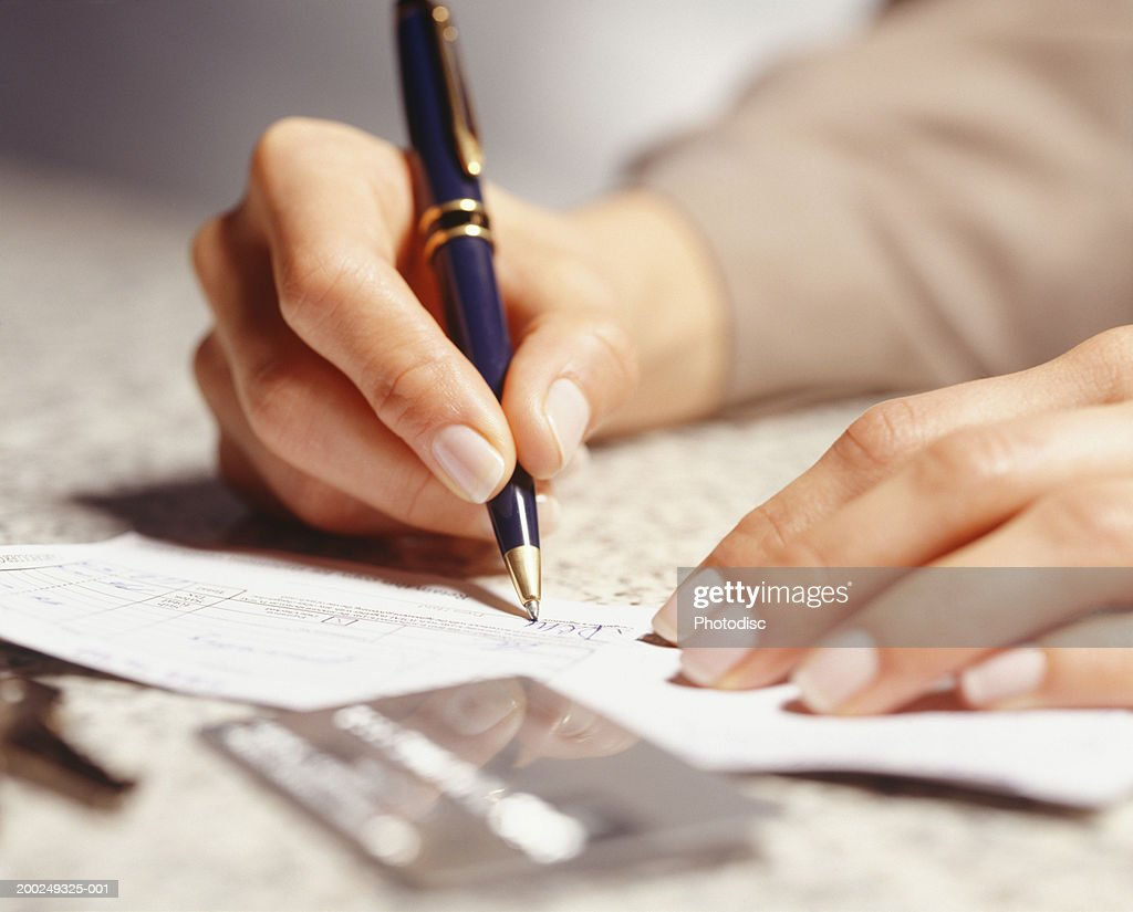 Woman signing receipt, Close-up of hands : Stock Photo