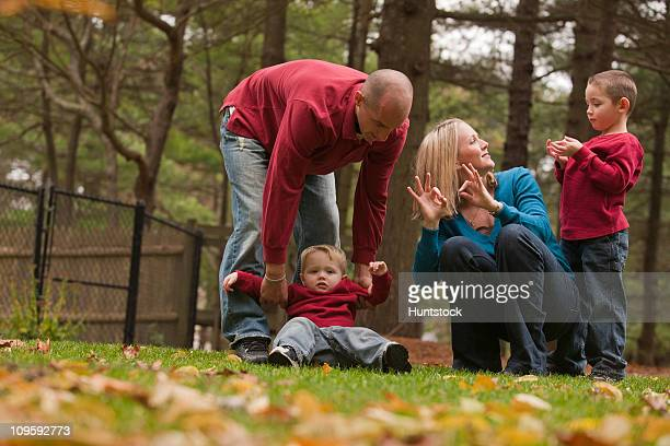 Woman signing the word 'Family' in American Sign Language while playing with her family in a park