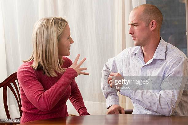 Woman signing the word 'Fine' in American Sign Language while communicating with a man