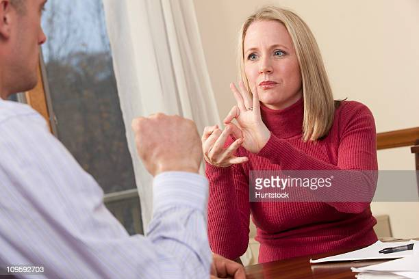 Woman signing the word 'Interpreter' in American Sign Language while communicating with a man