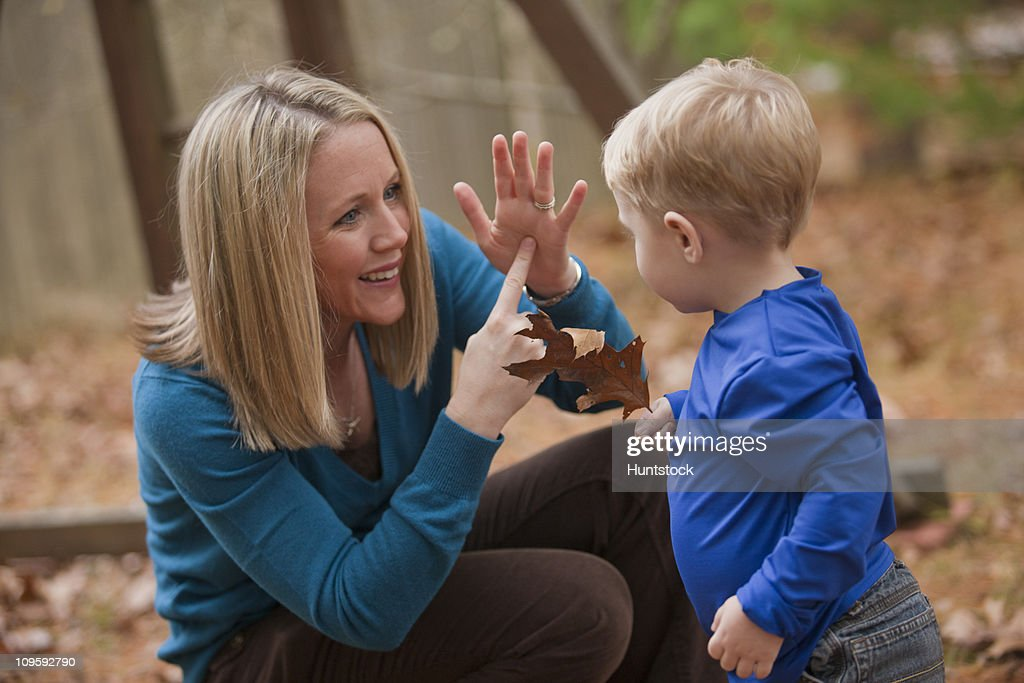 Woman signing the word 'Leaf' in American Sign Language while communicating with her son : Stock Photo