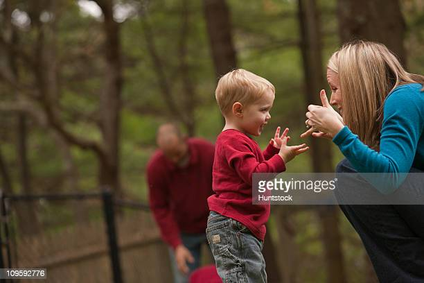 Woman signing the word 'Play' in American Sign Language while communicating with her son in a park