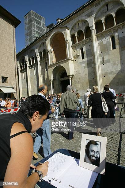 A woman signs a book of condolence at the entrance of Modena's Duomo where the coffin of Maestro Luciano Pavarotti lies in state on September 07 2007...