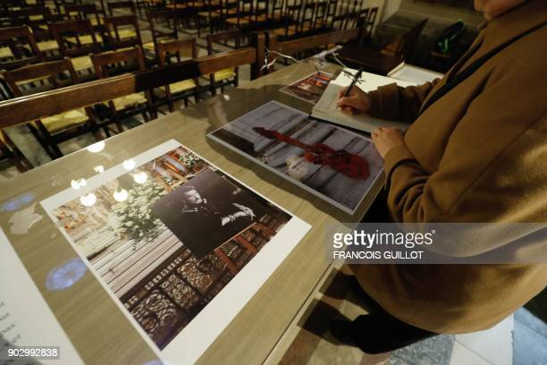 A woman signs a book of condolence for the late French musician Johnny Hallyday at La Madeleine Church in Paris on January 9 2018 French music icon...
