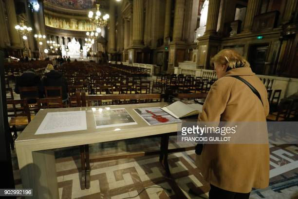 A woman signs a book of condolence to the late French musician Johnny Hallyday at La Madeleine Church in Paris on January 9 2018 French music icon...