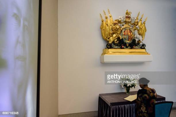 A woman signs a condolence book at the British Consulate in Hong Kong on March 23 after an attack in London on March 22 in which at least four people...