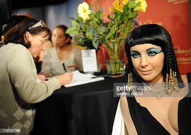 "A woman signs a condolence book beside a wax figure of Elizabeth Taylor in one of her most famous roles ""Cleopatra"" at Madame Tussauds in Hollywood..."