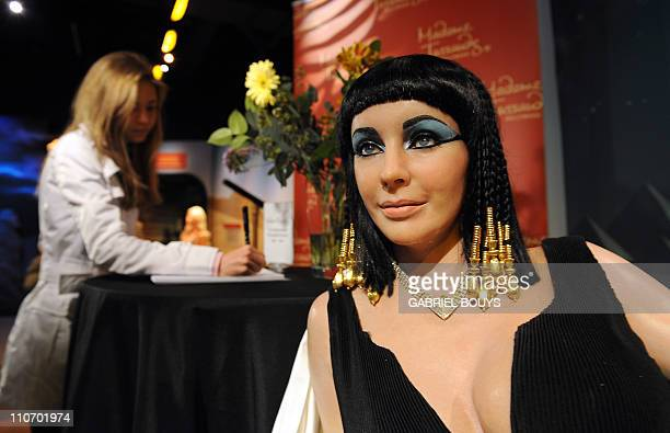 """A woman signs a condolence book beside a wax figure of Elizabeth Taylor in one of her most famous roles """"Cleopatra"""" at Madame Tussauds in Hollywood..."""