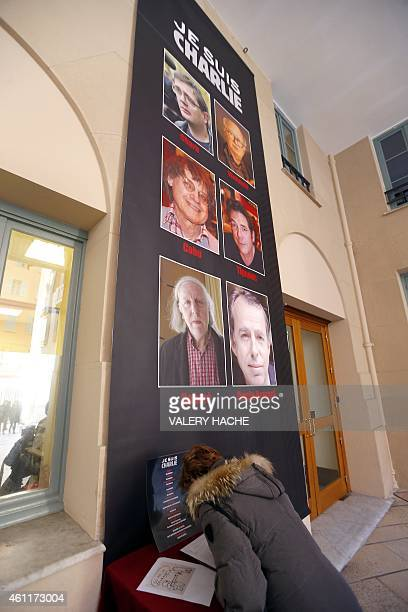 A woman signs a condolence book near a banner reading Je suis Charlie featuring the portraits of late Charlie Hebdo editor Stephane Charbonnier late...