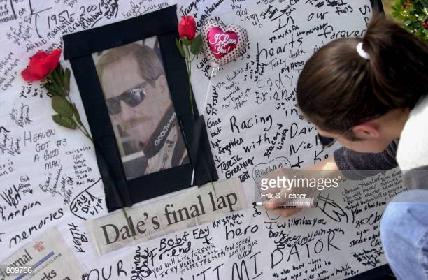 A woman signs a condolence card at a makeshift memorial for NASCAR driver Dale Earnhardt February 21 2001 at Atlanta Motor Speedway in Hampton...