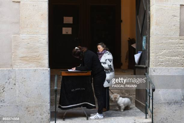 A woman signs a condolences book at the entrance to the church of SaintFeliud'Avall on December 15 a day after some children from the town were...