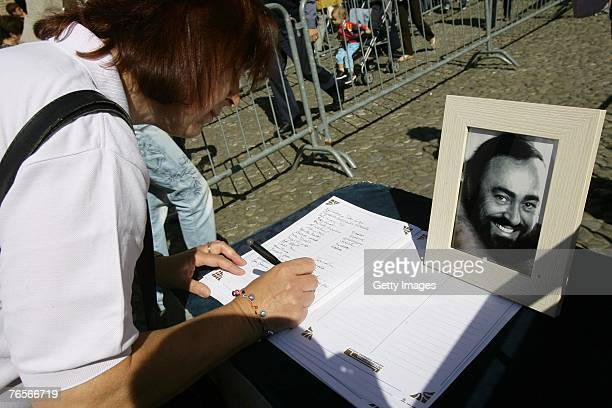 A woman signs abook of condolence at the entrance of Modena's Duomo where the coffin of Maestro Luciano Pavarotti lies in state on September 07 2007...