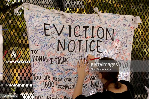 A woman signs an 'eviction notice' for President Donald Trump hanging on the security fence that surrounds the White House November 08 2020 in...