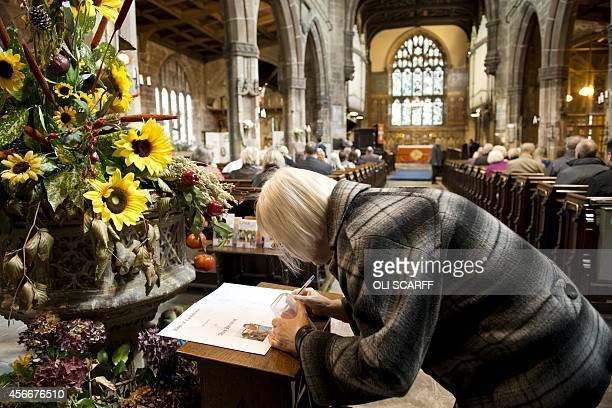 A woman signs the book of condolence in memory of murdered aid worker Alan Henning in Eccles Parish Church in Eccles north west England on October 5...