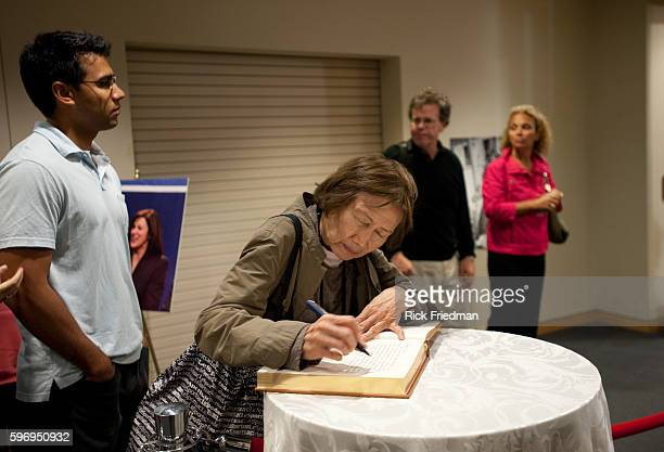 A woman signs the condolence book as she waits to pass by the casket containing the body of Senator Edward M Kennedy at the John F Kennedy Library in...