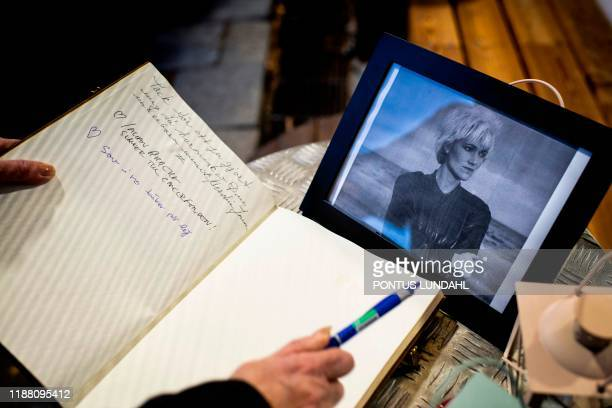 Woman signs the condolences book at a makeshift memorial for Swedish pop singer and songwriter Marie Fredriksson outside Baggpipe Studios in...