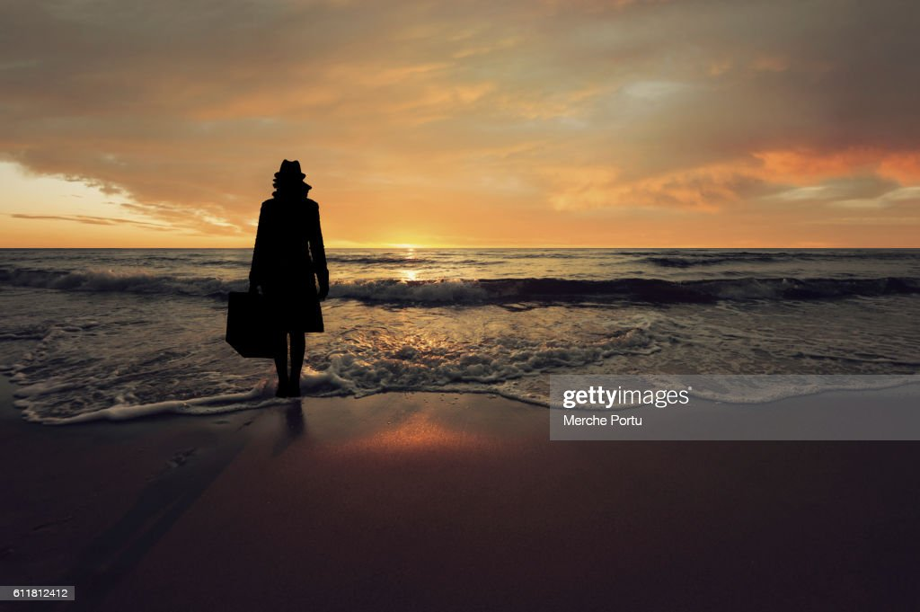 Woman silhouette with suitcase on the beach at sunset : Stock-Foto