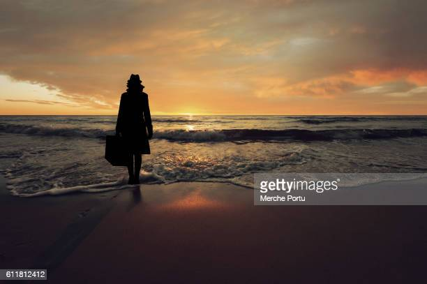 Woman silhouette with suitcase on the beach at sunset