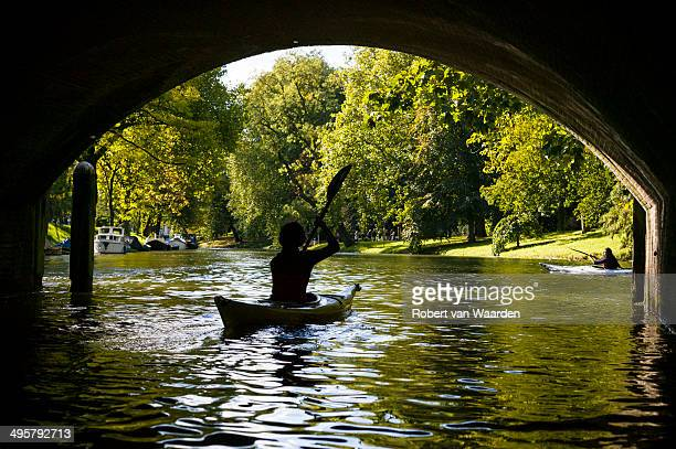 a woman silhouetted under a bridge while kayaking on the canals of utrecht, the netherlands. - utrecht stockfoto's en -beelden