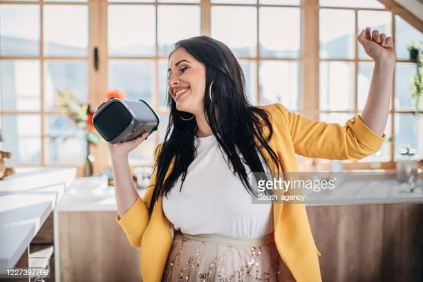 自宅で歌ったり踊ったり、ワイヤレスブルートゥーススピーカーを持っている女性 - ブルートゥース ストックフォトと画像