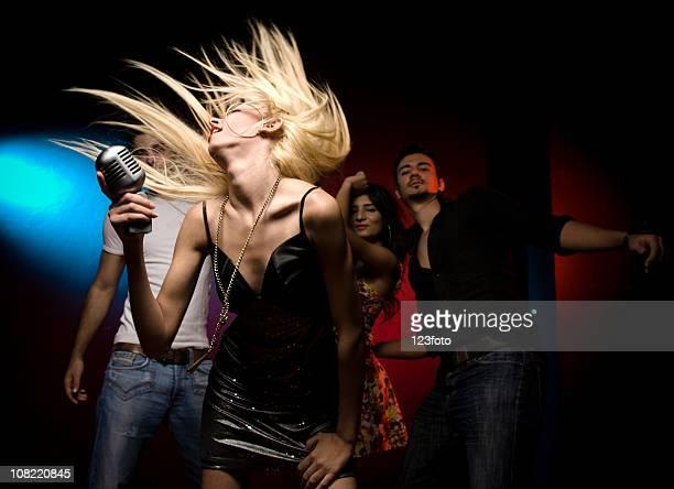 Donna cantare e ballare con folla dietro sua