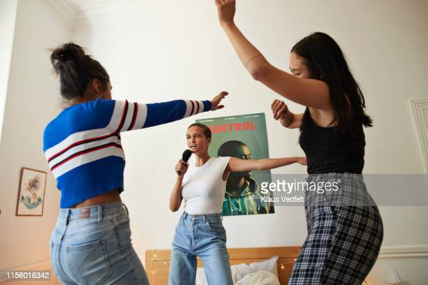 woman singing and dancing with friends at home - slumber party stock pictures, royalty-free photos & images