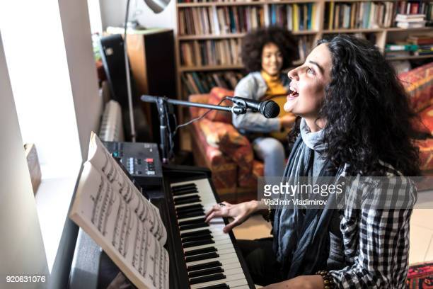 woman singing and playing the piano - keyboard player stock photos and pictures