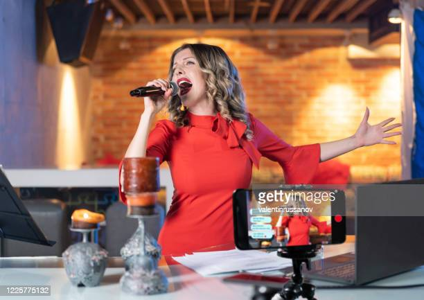 woman singing from empty discotheque and making video online teleconferencing during covid-19 - singer stock pictures, royalty-free photos & images