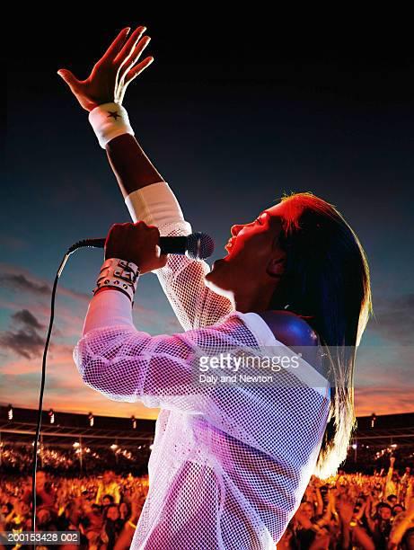woman singing, holding microphone, arm raised, crowd in background - concierto de música pop rock fotografías e imágenes de stock