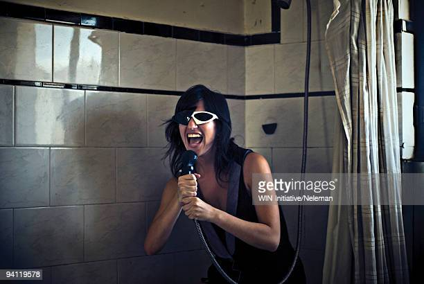 Woman singing into a shower head, Buenos Aires, Argentina