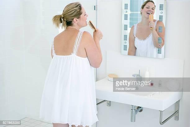 Woman Singing into Hairbrush in Bathroom
