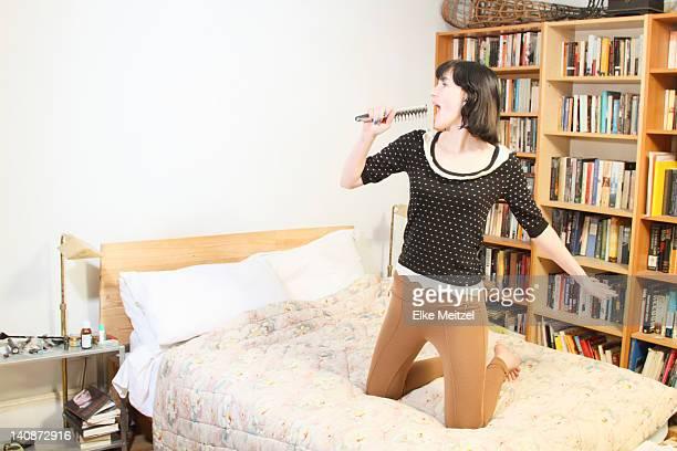 女性ヘアブラシを歌うとベッド