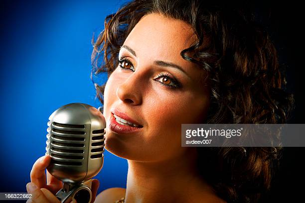Woman singing into microphone against blue background