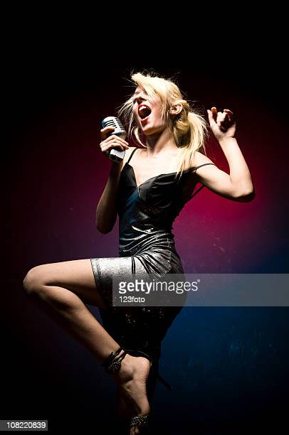 woman singing into microphone and dancing - blonde female singers stock photos and pictures