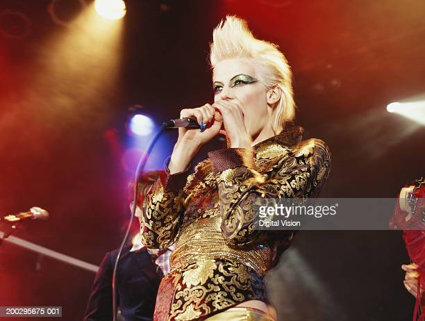 Woman singing into microphone, low angle view