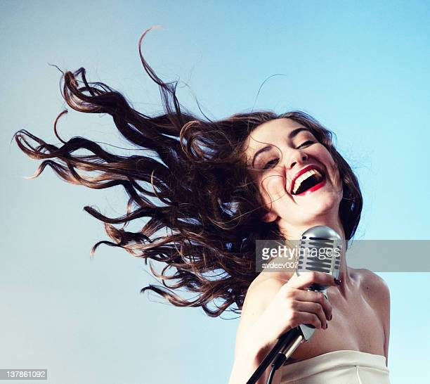 woman singing into microphone - pop musician stock photos and pictures