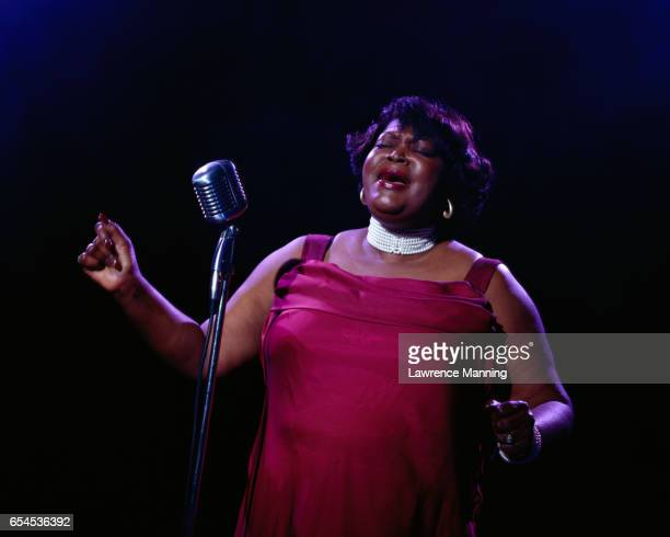 woman singing into microphone - soul music stock pictures, royalty-free photos & images