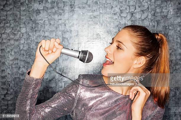 Woman Singing Karaoke Against Wall At Nightclub