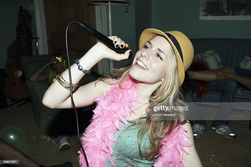 Woman singing karaoke at house party : Stock Photo