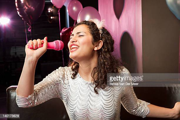 Woman singing karaoke in microphone.
