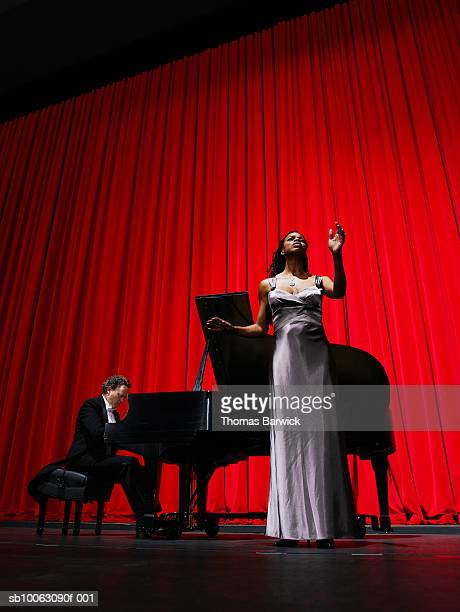 Woman singing on stage accompanied by male pianist