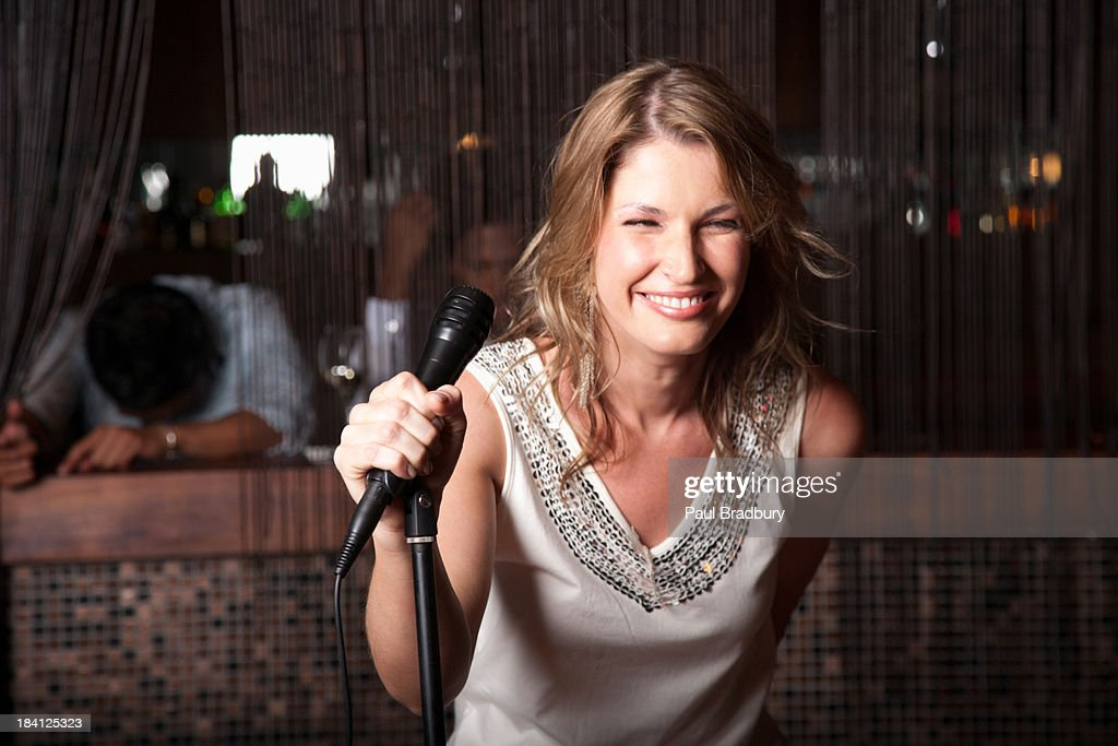 Woman singing out at a club : Stock Photo