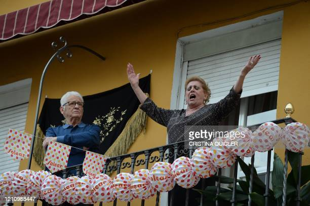 Woman sings as residents mark traditional April Fair from their adorned balconies on April 24, 2020 due to a national lockdown to prevent the spread...
