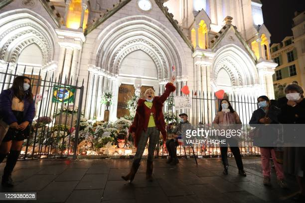 "Woman sings the ""Marseillaise"", the French national anthem, outside Notre-Dame de l'Assomption Basilica in Nice on October 31 to pay tribute to the..."