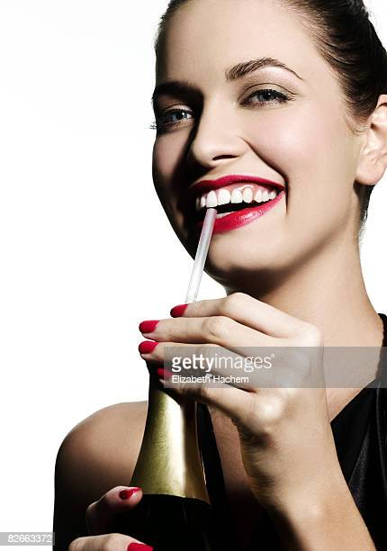 Woman sipping champagne through a straw