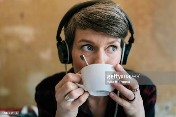 A Woman Sipping Coffee And Listening To Music