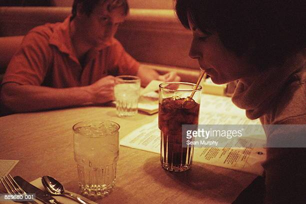 woman sipping drink, man across table - woman sitting on man's lap stock pictures, royalty-free photos & images